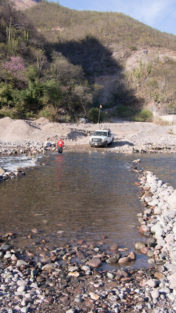 Stefan walking the river, as a truck with luggage and passengers waits to cross.